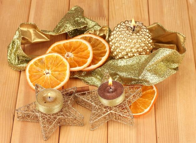 Composition de noël avec des bougies et des décorations sur fond de bois