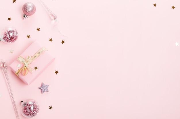Composition de noël. boule de noël décoration rose avec ruban sur fond rose.