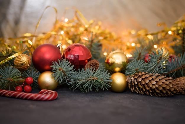 Composition de noël de boules d'or et rouges, bonbons, guirlandes, branches de sapin, cônes de sapin.
