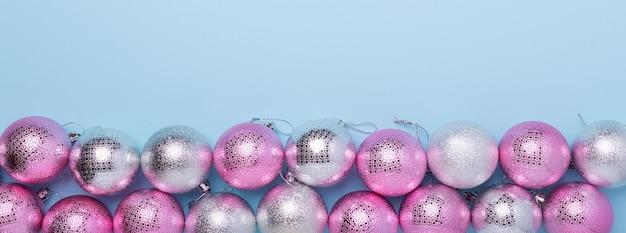 Composition de noël boules roses et argentées sur fond bleu pastel. bannière web. noel, hiver, concept de nouvel an. mise à plat, vue de dessus, espace de copie - image