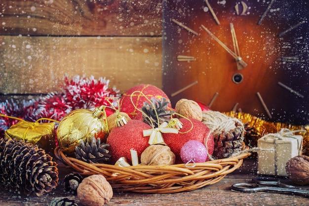 Composition de noël boules rouges et jaunes, cônes, vieille horloge dans un panier en bois. style vintage. tonifiant