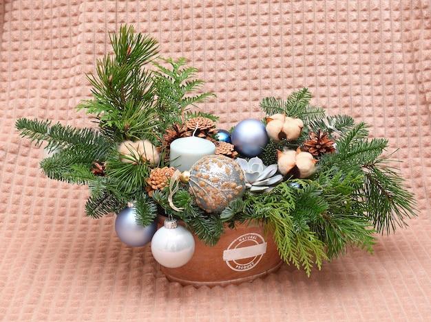 Composition de noël de branches de pin, de cônes, de coton, de boules et de bougies. photo en gros plan. sur fond beige