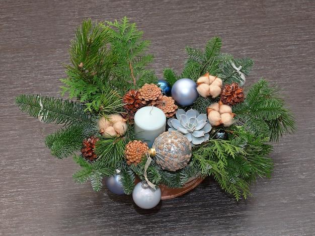 Composition de noël de branches de pin, de cônes, de coton, de boules et de bougies. photo en gros plan. sur fond sombre