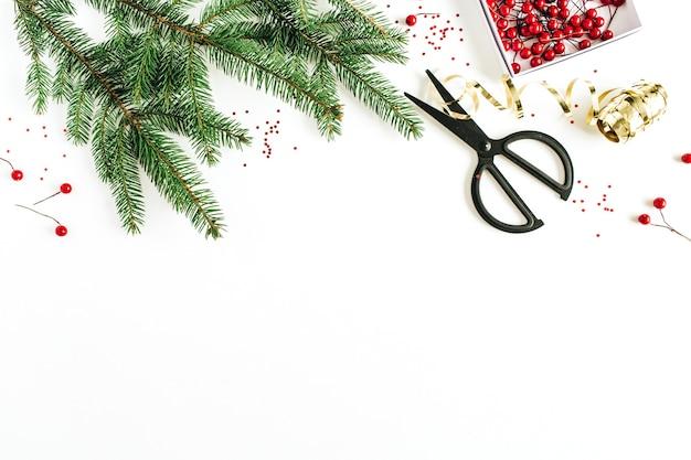 Composition de noël avec des branches de sapin, des baies rouges et des décorations sur une surface blanche. mise à plat, vue de dessus