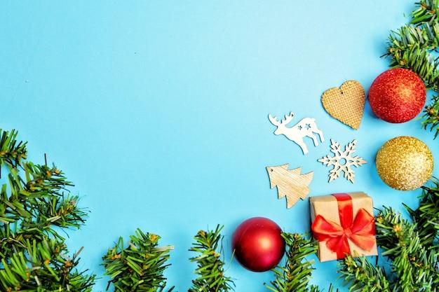 Composition de noël avec des branches de sapin, des ballons dorés et rouges, des jouets en bois sur fond bleu.