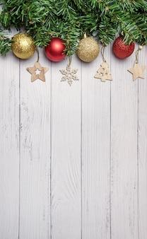 Composition de noël avec des branches de sapin, des ballons dorés et rouges, des jouets en bois sur un fond en bois blanc.