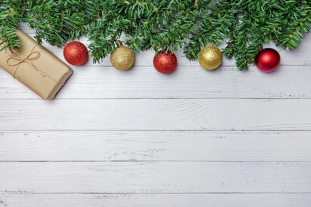 Composition de noël avec des branches de sapin, des ballons or et rouges et des cadeaux en papier craft sur un fond en bois blanc.