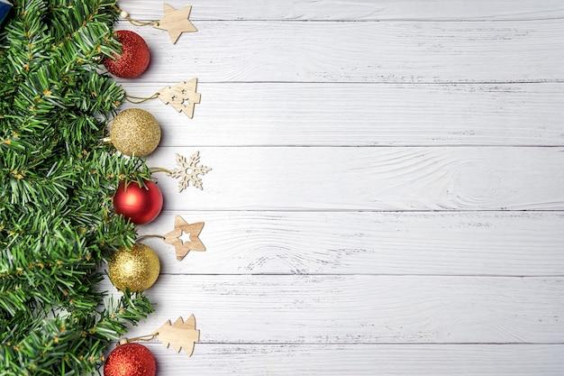 Composition de noël avec des branches de sapin, des ballons or et rouges sur un fond en bois blanc.
