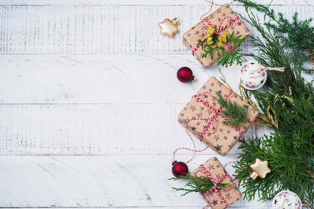 Composition de noël avec des branches de sapin, boîte-cadeau et boules sur table en bois. vue de dessus avec espace de copie.