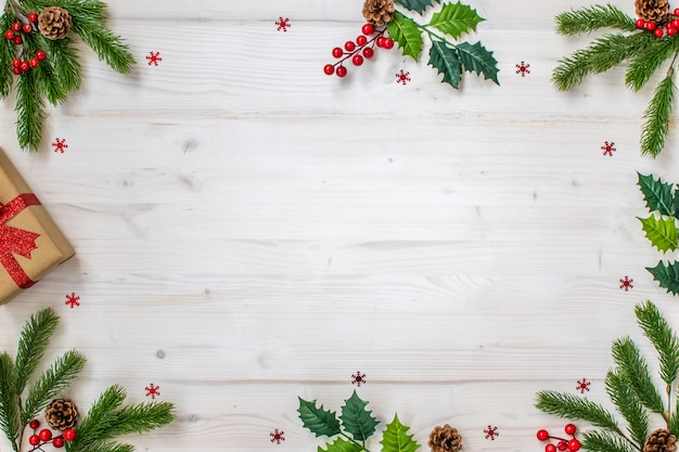Composition de noël avec des branches de sapin, des bonbons, des cadeaux, des pommes de pin et des étoiles sur du bois clair