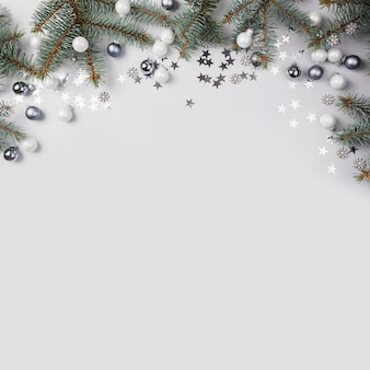 Composition de noël avec des branches de sapin, boules d'argent sur fond gris. carte de joyeux noël. vacances d'hiver. .