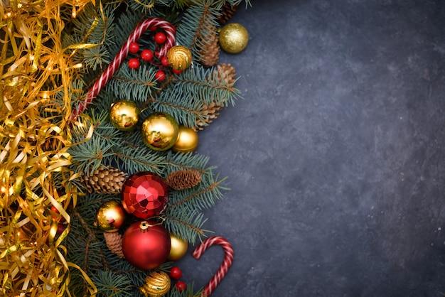 Composition de noël de branches de sapin, boules de noël, bonbons et pomme de pin sur noir