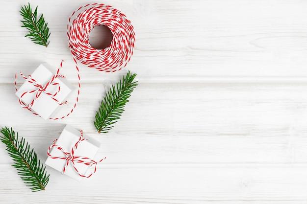 Composition de noël branches de sapin cadeau de noël sur fond blanc en bois vue de dessus à plat