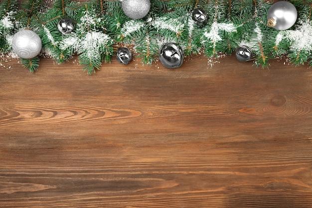Composition de noël avec des branches de sapin et décoration festive sur fond de bois