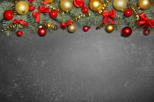 Composition de noël avec des branches de sapin et décoration festive sur fond gris