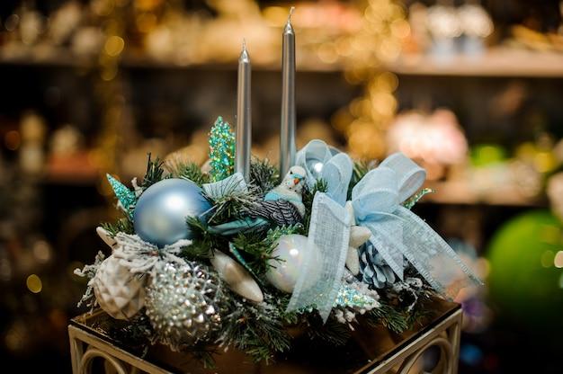 Composition de noël de branches de sapin, deux bougies, bandes, ornements bleus et argentés