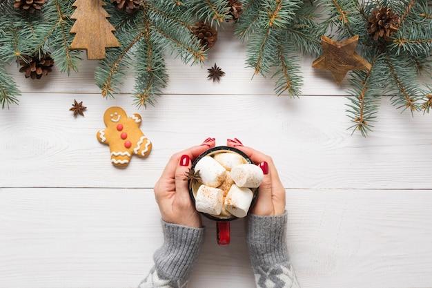 Composition de noël de branches de sapin, de jouets en bois et de café confortable avec des guimauves sur planche de bois. vue de dessus.
