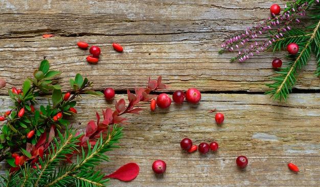 Composition de noël avec bruyère de sapin et berryes sur fond de bois rustique