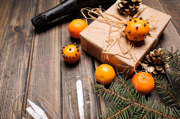 Composition de noël sur un bureau en bois avec boîte-cadeau, mandarines, pommes de pin et deux verres empy