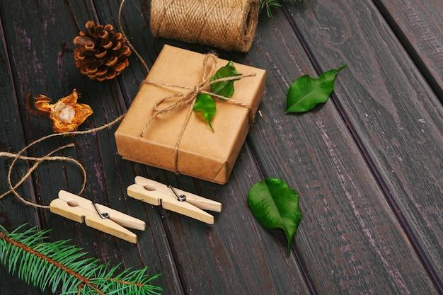 Composition de noël. cadeau de noël, couverture tricotée, pommes de pin, branches de sapin sur fond en bois.