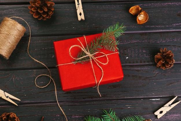 Composition de noël. cadeau de noël, couverture tricotée, pommes de pin, branches de sapin sur table en bois.