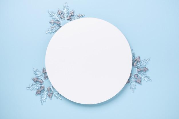 Composition de noël avec des cadeaux en argent. forme de cercle vierge de papier blanc sur fond bleu. modèle de noël. mise à plat, vue de dessus, espace de copie - image