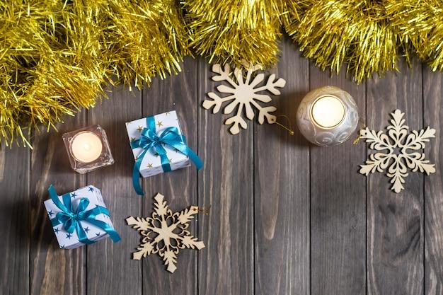 Composition de noël avec des cadeaux, des bougies et des flocons de neige décoratifs