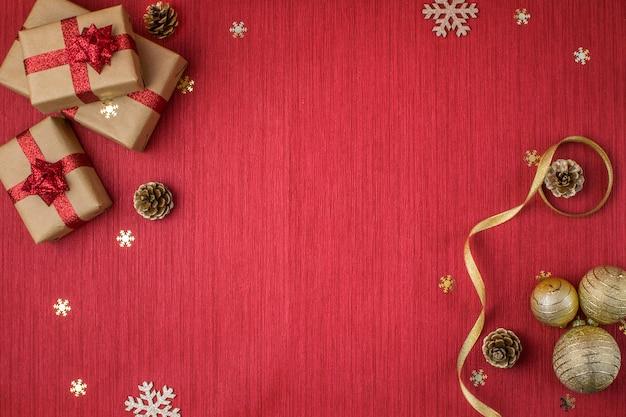 Composition de noël avec des cadeaux, des boules d'or, des pommes de pin, des branches de sapin et des flocons de neige sur un rouge
