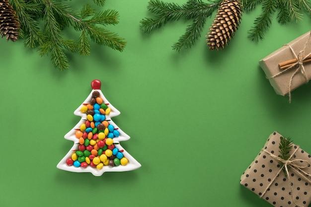 Composition de noël. cadeaux et branches d'épinette. une assiette sous la forme d'un arbre de noël rempli de bonbons colorés sur fond vert. mise à plat, vue de dessus, espace copie