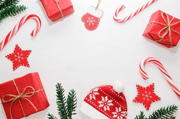 Composition de noël cadeaux, branches de sapin, décorations rouges sur fond blanc.