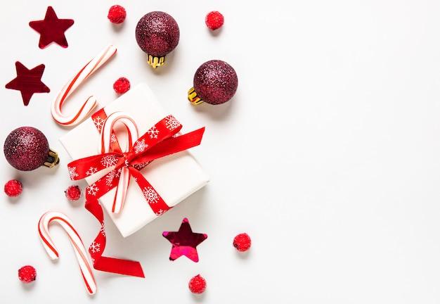 Composition de noël. cadeaux, canne en bonbon et décorations rouges sur fond blanc. noël, hiver, concept de nouvel an. mise à plat, vue de dessus, espace copie