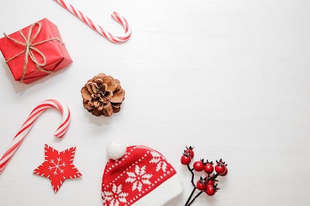 Composition de noël cadeaux, cônes de sapin, décorations rouges sur fond blanc.