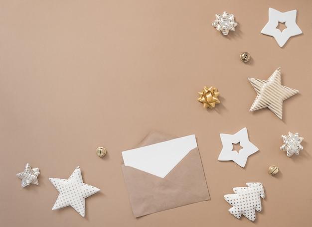 Composition de noël. cadeaux, enveloppe artisanale et décorations dorées sur fond blanc. mise à plat, vue de dessus, espace copie
