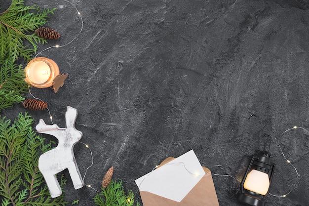 Composition de noël cadeaux, enveloppe, branches de sapin, décorations blanches sur fond noir. noël, hiver, concept de nouvel an. lay plat, vue de dessus, espace de copie