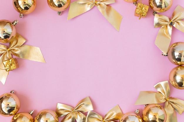 Composition de noël cadeaux de noël, décorations dorées sur rose pastel