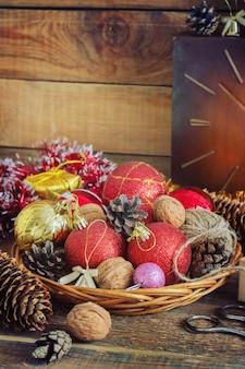 Composition de noël avec des cadeaux. panier, boules rouges, pommes de pin, flocons de neige sur une table en bois. style vintage