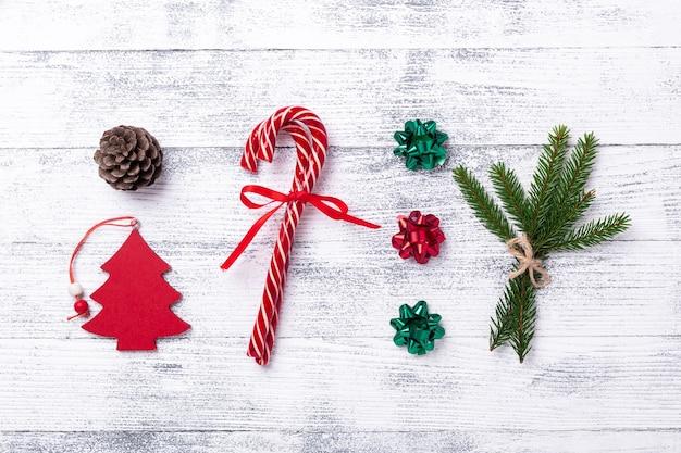 Composition de noël. cadeaux rouges, sapin, branche et cône de sapin, cannes de bonbon sur fond en bois. mise à plat, vue de dessus - image