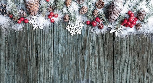 Composition de noël. cadre fait de branches de sapin, de cônes et de baies de noël rouges recouvertes de neige sur fond de bois ancien. vue de dessus, mise à plat, espace de copie