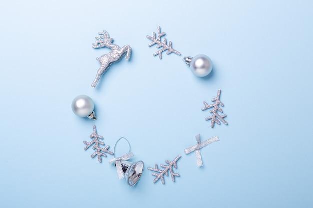 Composition de noël. cadre fait de décoration argentée sur fond bleu pastel. noel, hiver, concept de nouvel an. mise à plat, vue de dessus, espace de copie - image