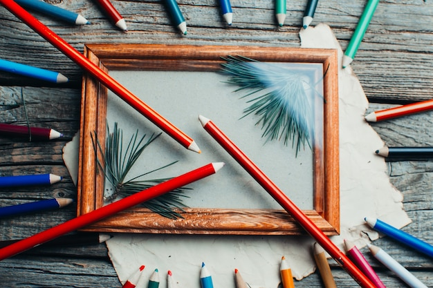 Composition de noël, cadre photo sur table en bois, avec des branches d'arbres autour des crayons éparpillés de différentes couleurs