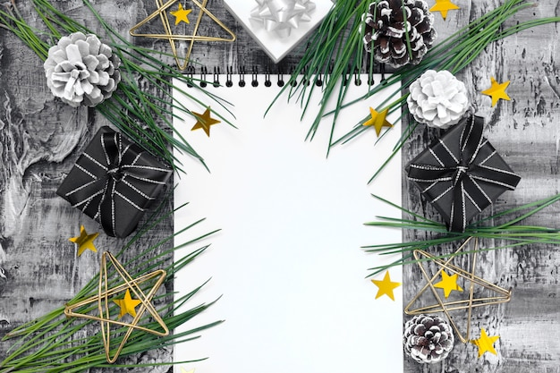 Composition de noël avec cahier, branches de sapin, étoiles dorées et coffrets cadeaux