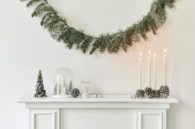 Composition de noël sur la cheminée blanche à l'intérieur du salon avec une belle décoration. arbre de noël et couronne, bougies, étoiles, lumière. espace de copie. modèle.