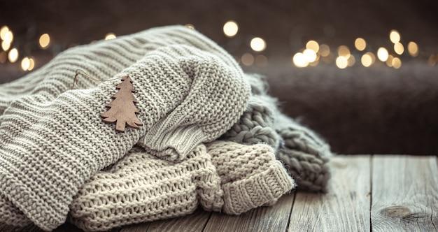 Composition de noël confortable avec une pile de pulls tricotés sur un arrière-plan flou avec bokeh.