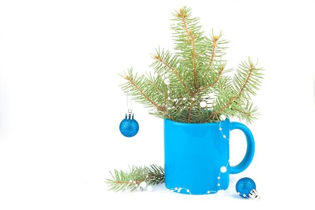 Composition de noël dans une tasse de thé bleu, branches d'épinette, boules. couleur bleu classique