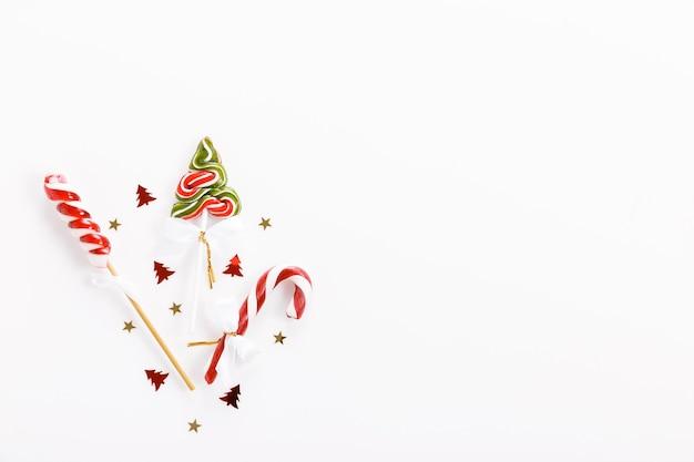 Composition de noël. décor rose de noël, canne en bonbon de noël avec ruban sur fond blanc.