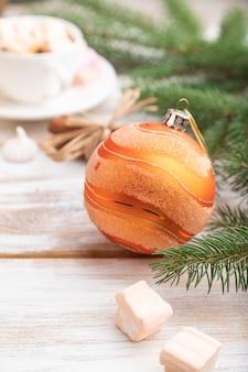 Composition de noël. décorations, boîte, boules, branches de cannelle, de sapin et d'épinette, tasse de café sur table en bois blanc.