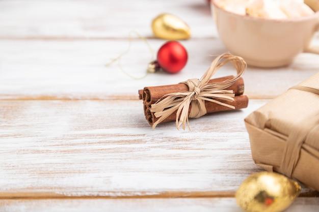 Composition de noël. décorations, boîte, boules rouges, branches de cannelle, de sapin et d'épinette, tasse de café sur table en bois blanc.