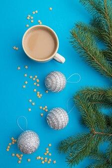 Composition de noël. décorations, boules d'argent, branches de sapin et d'épinette, tasse de café sur papier bleu. mise à plat.