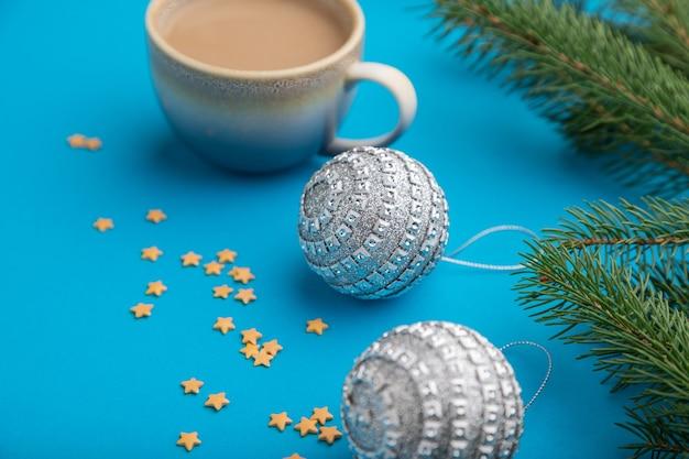 Composition de noël. décorations, boules d'argent, branches de sapin et d'épinette, tasse de café sur papier bleu.