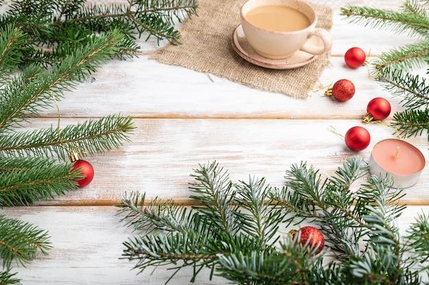 Composition de noël. décorations, boules rouges, branches de sapin et d'épinette, tasse de café, bougies sur table en bois blanc.